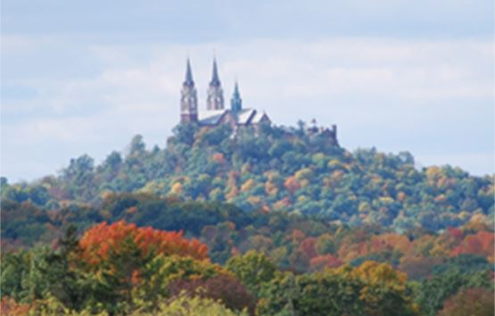 Church steeple seen in the distance surrounded by an early fall forest